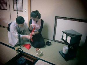 The Sensei is helping fold the handkerchief correctly.