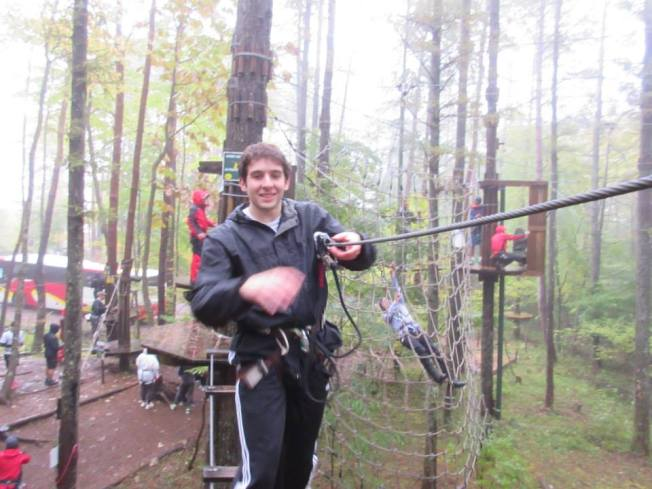 "After losing his balance, Gabe cheats a little and grabs hold onto the zip-line to complete this course. Meanwhile, in the background, I ""Tarzan swung"" into a net."