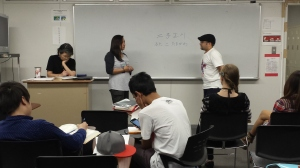 Students present their dialogue to the class as sensei follows along and checks their memorization.