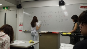 A brave student volunteers to write on her answers on the board.