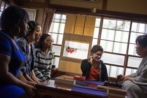 Jennifer Hayes, Naomi Polite, Kay James, and Louisa Lightfoot are taught how to do Calligraphy.