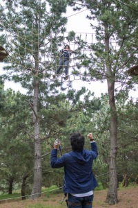 TUJ student Nick Watanabe cheers on his fellow classmate Dina Pakstis as she takes on the adventure course.