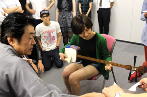 TUJ student happily playing the shamisen for the first time.