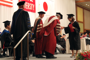 TUJ graduate shaking the Temple University's President Neil D. Theobald hand after receiving her diploma.