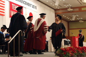 TUJ MBA graduate shaking the hand of Temple University's main campus President Neil D. Theobald.