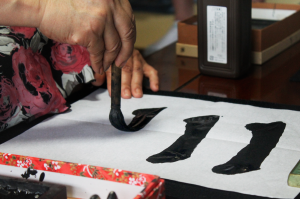 Host demonstrating an exercise that helps to practice proper form and technique for calligraphy.