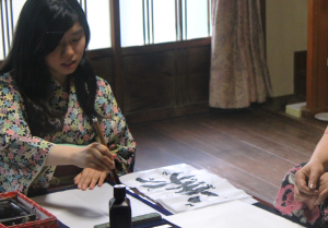 Female TUJ student writing out her character (kanji).