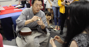 Ichinosuke teaching a TUJ student how to properly bandage her fingers before playing the Shamisen.