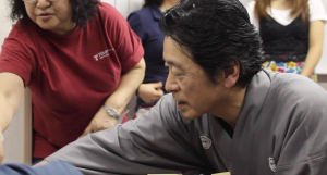 Ichinosuke taking the time to instruct TUJ students on proper form and technique for playing the shamisen.