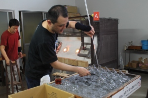 TUJ instructor cuts glass off the glass blowing stick after they are done